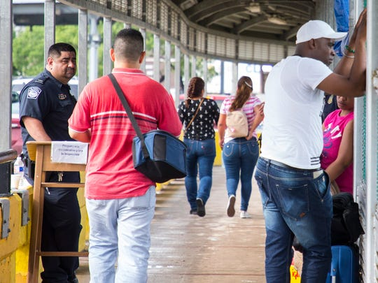 Immigrants seeking asylum in the U.S. stand along a fence after being turned away by U.S. Customs and Border Protection agents at the border in Brownsville, Texas, on Thursday, June 21, 2018.