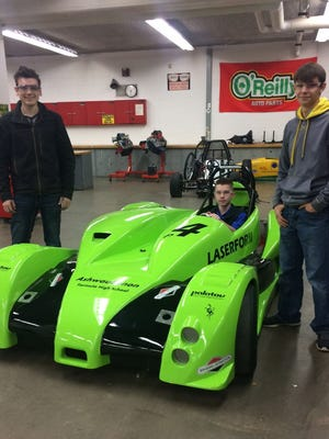 Flanked by junior Brandon Reckelberg, left, and sophomore Russell Coble, right, junior Conhur Alvis sits in the cockpit of a replica race car designed and built by Ashwaubenon High School students who are in the school's Formula Student program.