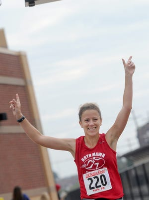 This file photo shows Katie O'Regan of Lebanon raising her hands in victory after she is the first female to cross the finish line of the White Rose 5-Mile-Run at Sovereign Bank Stadium in York city on Saturday, Sept. 28, 2013.