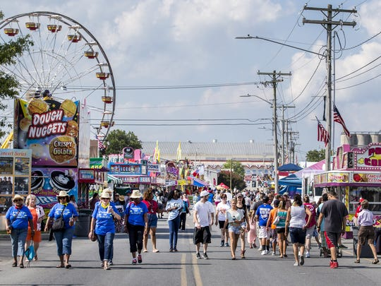 Fairgoers make their way through the Delaware State Fairgrounds in Harrington last year.