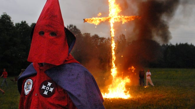 A Ku Klux Klansman takes part in a cross-lighting ceremony in a field near Vina, Ala., after an anti-immigration rally.