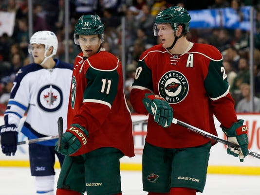 FILE- In this Nov. 27, 2015, file photo, Minnesota Wild left wing Zach Parise (11) talks with defenseman Ryan Suter (20) during the second period of an NHL hockey game against the Winnipeg Jets in St. Paul, Minn. Forever linked as the players who lifted the Wild franchise's profile around the league, the duo's leadership will be counted on this spring as the they try to reach the Stanley Cup finals for the first time. (AP Photo/Ann Heisenfelt, File)