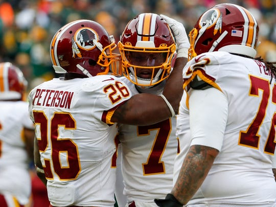 Washington Redskins' Adrian Peterson celebrates his touchdown run with Dwayne Haskins during the first half of an NFL football game against the Green Bay Packers Sunday, Dec. 8, 2019, in Green Bay, Wis. (AP Photo/Matt Ludtke)