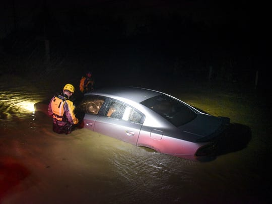 Rescue staff from the Municipal Emergency Management Agency investigate a flooded car during the passage of Hurricane Irma through the northeastern part of the island in Fajardo, Puerto Rico.