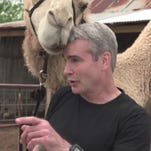 A camel tries to interrupt Henry Rollins as he interviews a camel farmer.