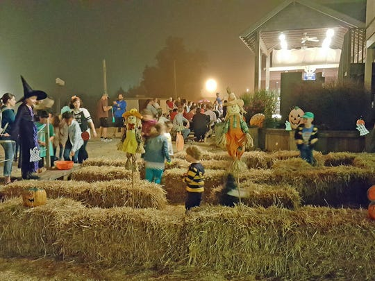 Children walk through a hay maze, one of the non-scary
