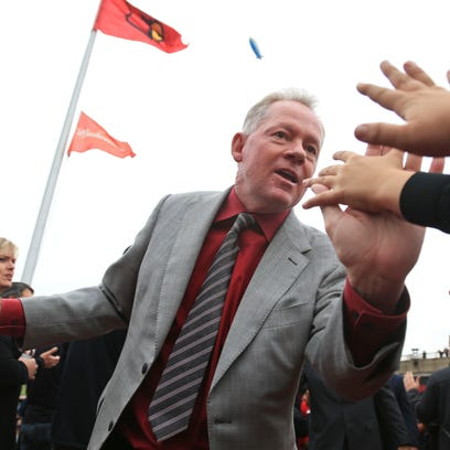 Louisville coach Bobby Petrino greets fans before the