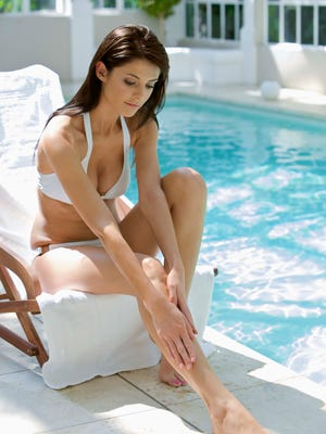 Woman in lounge chair by swimming pool