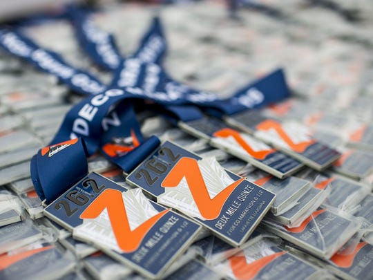 Medals for marathon and half-marathon race finishers are prepared for distribution at the finish line during the 2015 Zydeco Marathon in Lafayette.