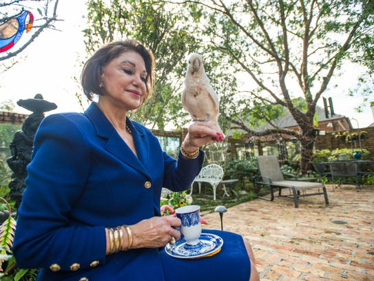 Carolyn French holds her bird, named Angel, as she