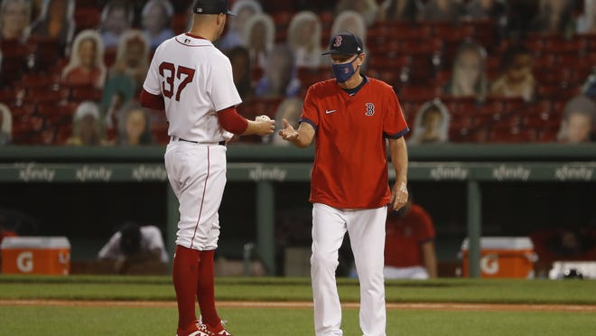Red Sox manager Ron Roenicke reaches to take the ball from former relief pitcher Heath Hembree after he gave up a three run home run to Phillies outfielder Bryce Harper. Roenicke has had to make frequent trips to the mound this season.