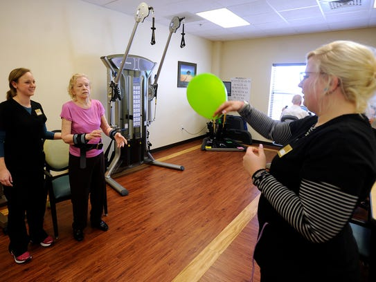 Rehab tech Robin Wadsworth, right, hits a balloon to