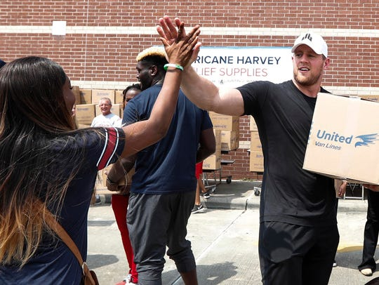 Anna Ucheomumu, left, high fives Houston Texans defensive