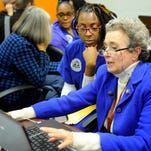 Jackie Shrago, a volunteer with Get Covered Tennessee, navigates the healthcare.gov website to help Connie Austin sign up for insurance through the Affordable Care Act in the 2015 open enrollment season.