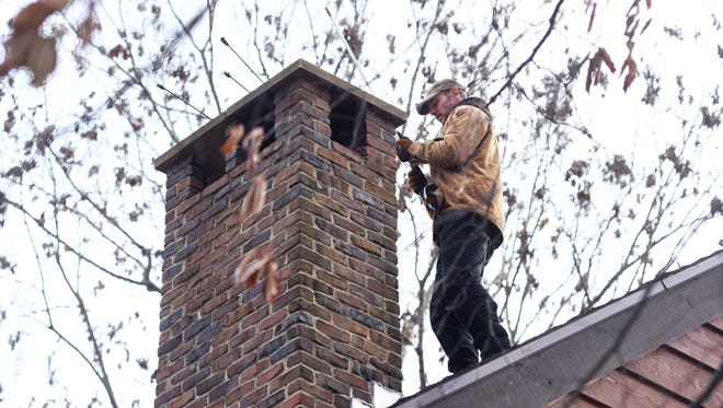 Brock Brocklehurst readies his equipment for cleaning chimneys at a home in Zanesville recently. Brocklehurst uses a drill with a long rotating brush at the end for much of the cleaning.