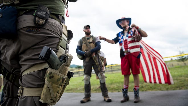 Armed civilians listen as Helena Rodriguez, right, of Reading, speaks with them near a demonstration area at Gettysburg National Military Park on July 1, 2017.