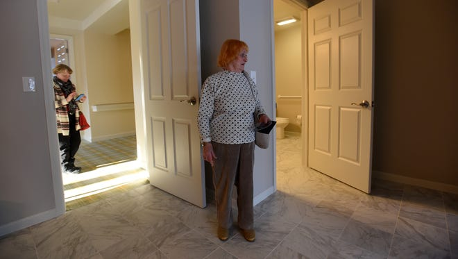 Nancy Siegel (center) looks around her new apartment as her daughter, Lesa Miller, sends photos of the space to another family member. Siegel attended the open house hosted by Middleton Senior Living to unveil its new living units on Wednesday, Jan. 17, 2018.