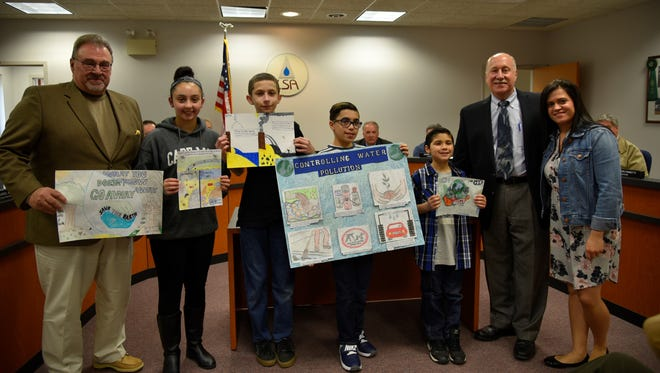 (From left) Carlos Villar, chairman, Landis Sewerage Authority, holding the poster by AdolfoLeonel from Wallace Middle School, Hannah Hargrave from Bishop Schad Regional School, James Schmidt from Creative Achievement Academy, Christian Perez from Rossi Intermediate School, Misael Martinez from Vineland Public Charter School, Dennis W. Palmer, executive director, LSA, and Marianette Arce, administrative secretary and Earth Day poster coordinator, LSA, are pictured at a recent LSA board meeting.