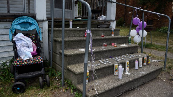 A baby stroller sits beside a makeshift memorial site on the steps of a Detroit home where 1-year-old  Ca'mya Davis died after falling through a hole in the floor to a water-filled basement, where she drowned.