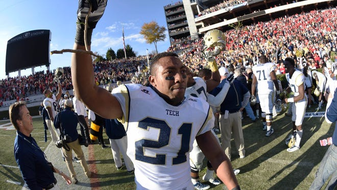 Georgia Tech running back Charles Perkins  takes a piece of Georgia's hedges after the Yellow Jackets won in overtime at Sanford Stadium.