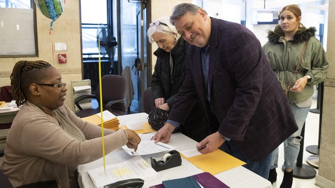 April Green, left, a public records aide, helps Joan Morgan, center, of Mt. Kisco, and Joseph Pessolano, second from right, from Staten Island, as they file their pre-adoption birth certificate application on Wednesday in New York.