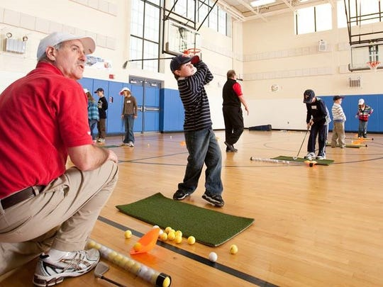 TGA Premier Junior Golf is the leading before and after-school golf enrichment program in the country, which takes place year round on school campuses and at community centers. Here Dave Robinson works with students on their golf games inside the gymnasium.