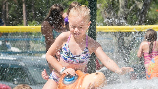 Ryleigh Watts, 7, is drenched with water as she sits on a turtle shaped fountain during the grand opening of the new Dolphin Island Splash Pad at Sunset Kids Park in Gulf Breeze on Wednesday, May 30, 2018.