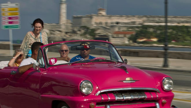 Tourists ride in a classic American car on the Malecon in Havana, Cuba in a photo from Oct. 15, 2014.