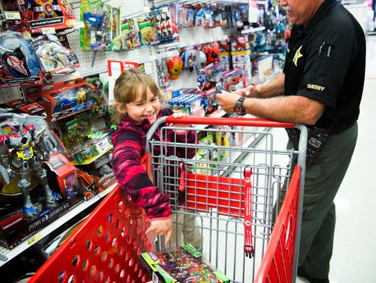 """Tatiana Cruz adds a gift for her brother to her cart during the """"Shop With a Sheriff"""" event at Target in North Naples on Thursday, Dec. 14, 2017. The Collier County Sheriff's Office and the Jewish Federation of Greater Naples partnered for the third year in a row to help 65 children and their families during the holiday season."""