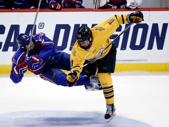 Quinnipiac's Tim Clifton (11) hits UMass Lowell's Chris Forney during the third period of the NCAA men's East Regional championship hockey game, Sunday, March 27, 2016, in Albany, N.Y. Quinnipiac won 4-1. (AP Photo/Mike Groll)