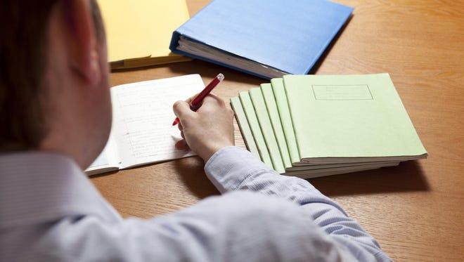 Teacher grading books.
