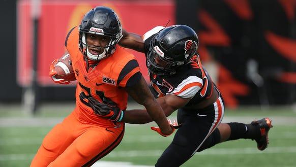 Oregon State's Artavis Pierce tries to get past Kee