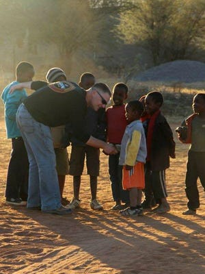 Steve Baker in Botswana meeting children who were being given food and aid.