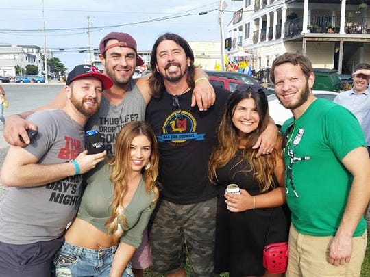 Foo Fighters' Dave Grohl poses with fans in Dewey Beach Saturday, July 30, 2016 including Debora Magalhães (front left).