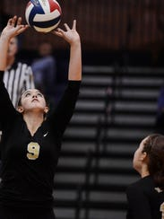Delone Catholic's Allie Mondorff, left, sets the ball as Cheyenne Altland goes up for a fake hit against South Western during the YAIAA girls' volleyball championship match at Dallastown on Tuesday. The Squirettes won in five sets. (Daily Record/Sunday News -- Kate Penn)