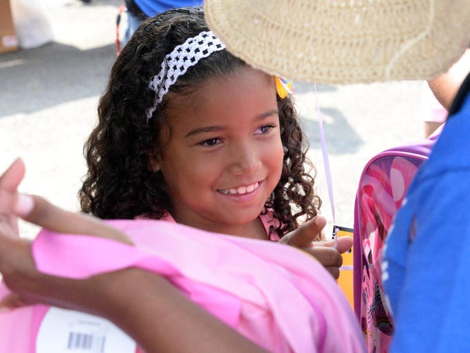 Luz Solano, 6, smiles while picking out a free book bag during Back to School Giveaway & Community Day at Greater Deliverance Church in Vineland on Saturday, August 16, 2014.  Staff photo/Charles J. Olson