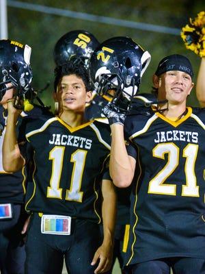 Menard's Noah Rosas (11) and Christian Salazar (21) raise their helmets to the school song as they enjoy a trip to Victory Hill after a 35-18 win over Rocksprings on Sept. 15, 2017.