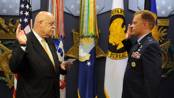 Retired Vermont Judge Edward Cashman, left, administers the oath Friday to his son, Air Force Brig. Gen. Jeffrey Cashman, in the Pentagon's Hall of Heroes.