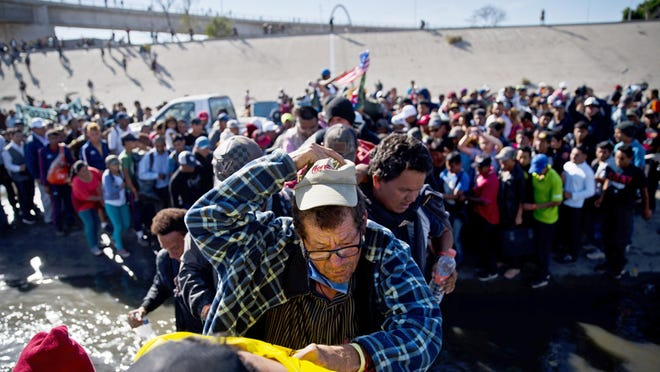 In this Nov. 25, 2018 file photo migrants cross the river at the Mexico-U.S. border after pushing past a line of Mexican police at the Chaparral crossing in Tijuana, Mexico, as they try to reach the U.S.