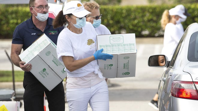 Volunteers distribute food at the Palm Beach Outlets in West Palm Beach Friday, July 10, 2020.  The supply of 516 boxes of food were given out in an hour.  The distribution was done in partnership with Schumacher Auto Group and The Tree of Life Resource Center, which offers grocery assistance and other resources to people in need during the pandemic. Farm Share's The Big Red Truck and Cotton Bottom Diaper Bank also participated in the event.
