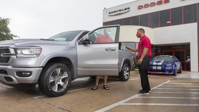 Salesman Landon Britt, right, talks with customer Steven Johnson as Johnson prepares to drive away in his newly purchased truck from Nyle Maxwell Supercenter in North Austin on Sept.17. Austin-area auto dealers say there are signs that sales are starting to recover from the slowdown caused by the coronavirus outbreak.