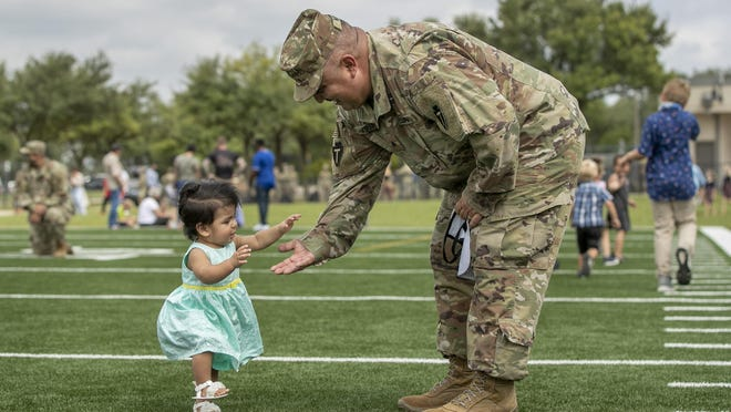 Sgt. David Moran III tries to teach his 9-month-old daughter, Penelope, to walk before he boarded a bus at the 36th Infantry Division deployment ceremony at Kelly Reeves Athletic Complex on Sunday. Seven hundred Texas National Guard soldiers were sent on a nine- to ten-month deployment to the Middle East for Operation Spartan Shield, which seeks to strengthen relations with partner nations.