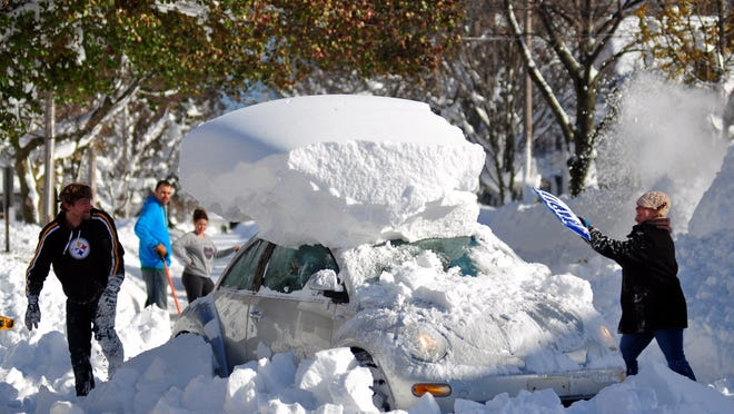 Michael Palmer and Carin Schultz work to clear her car of snow and remove it from Union street on November 20, 2014 in the suburb of Hamburg, Buffalo, New York.