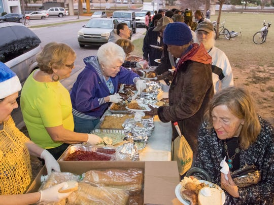 A long line of people make their way through the food table during a weekly meal served under the I-110 overpass on Lee Street in downtown Pensacola.
