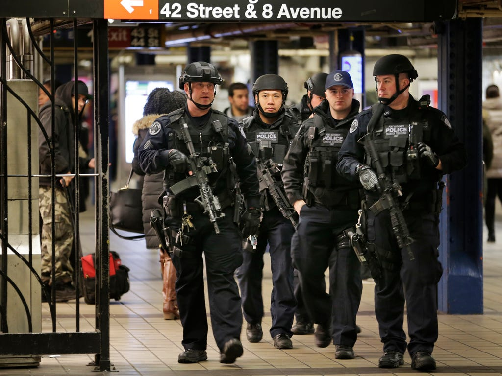 Police officers patrol in the passageway connecting New York City's Port Authority bus terminal and the Times Square subway station in New York, Dec. 12, 2017, near the site of Monday's explosion. Commuters returning to New York City's subway system
