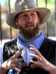 "Trevor Allen describes the early history of Abilene during his downtown walking tour June 15. Allen portrays cowboy poet ""Gus McDusty"" during the 90-minute outing, lyrically blending facts and history."