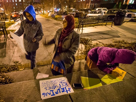 Iram Shaukat (center) looks at her 10-year-old son, Bassam Rafique, as he holds up a sign after making one with Iram and his sister, 8-year-old Rameen Rafique (right), at a vigil to show solidarity with refugees near the Soldiers and Sailors Monument in Wilmington on Wednesday night.
