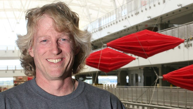 "Indianapolis artist Greg Hull is pictured with his kinetic sculpture, ""Breath,"" in the parking garage atrium at Indianapolis International Airport."