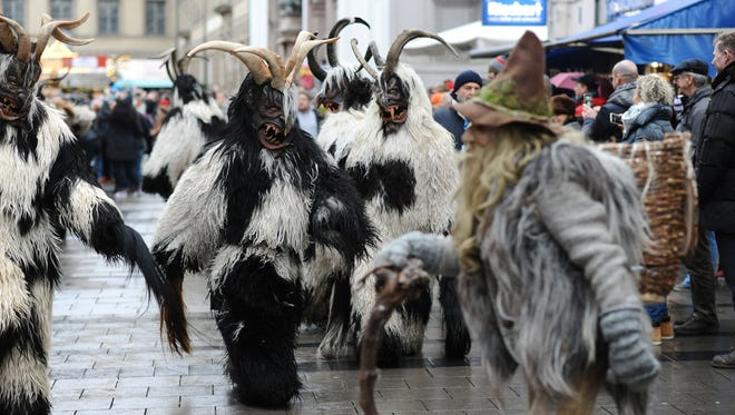 Masked participants dressed in traditional  Krampus  outfits parade during the Krampus Run near the Christmas Market in Munich, Germany, on Dec. 11, 2016. A Krampus is  a horned folklore figure described as half-goat, half-demon.   (Andreas Gebert/dpa via AP)