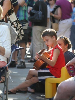 Cadon Hill, 7, plays his guitar while sitting with his mom, Rochelle Dalverth, during the Xerox Rochester International Jazz Festival in June 2014. Cadon and his mom live in Rochester. They were hanging out, checking out the activity, and Cadon was doing a little street performing.